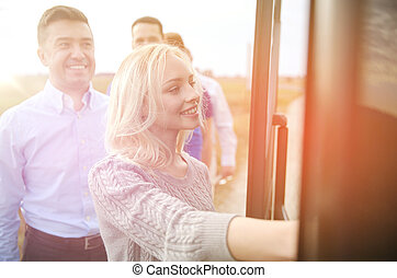 group of happy passengers boarding travel bus - transport,...
