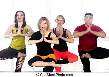 Group of happy people doing yoga training in class