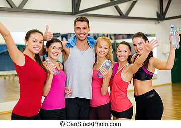group of happy people in gym with water bottles