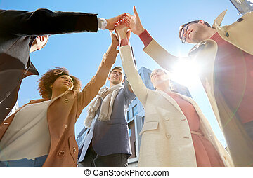 group of happy people making high five in city - business,...
