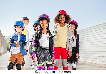 Group of happy sporty kids rollerblading outdoors