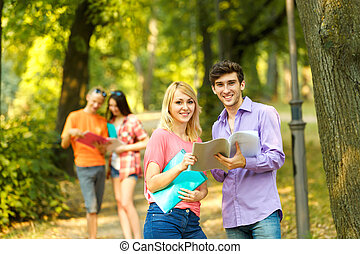 group of happy students with books in the Park on a Sunny day.