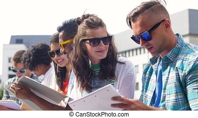 group of happy students with notebooks at campus - education...