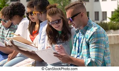 group of happy students with notebooks at campus -...