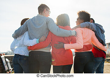 group of happy teenage friends hugging on street