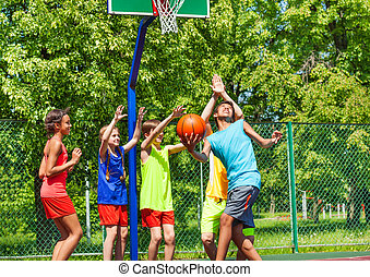 Group of happy teenagers playing basketball