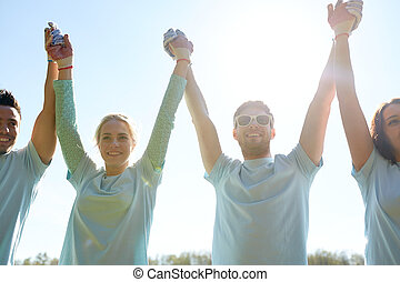 group of happy volunteers holding hands outdoors -...
