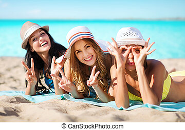 group of happy women in hats sunbathing on beach - summer...
