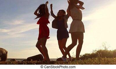 group of happy women or girls dancing on beach