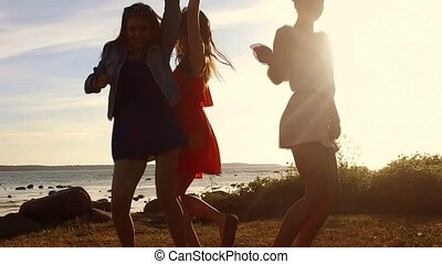 group of happy women or girls dancing on beach 51