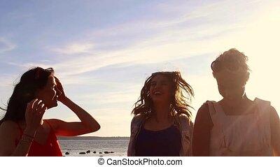 group of happy women or girls dancing on beach 46