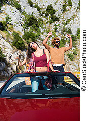Group of happy young people dancing in the red convertible.