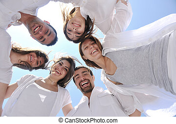 Group of happy young people in circle at beach have fun and...