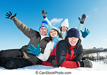 happy young smiling student people group in warm clothing lying on snow at winter outdoors