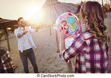 Group of happy young people playing with ball on beach
