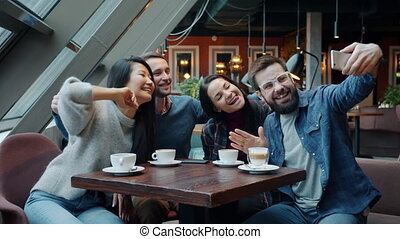 Group of happy young people taking selfie and having fun using smartphone camera in cafe