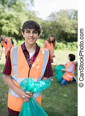 Group Of Helpful Teenagers Collecting Litter In Countryside