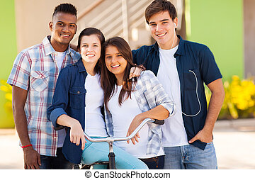 group of happy high school students with a bicycle outdoors