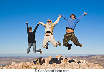 Group of hikers jumping cheerfully on mountain summit