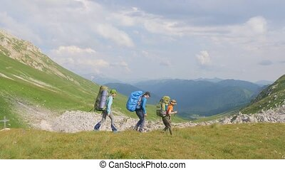 Group of hiking people traveling in mountain on green hills and sky background.