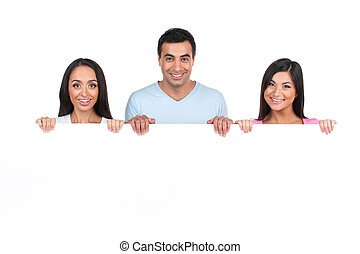 Group of Indian people standing behind blank poster. Mixed...