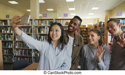Group of international students have fun smiling and making selfie photos on smartphone camera at university library. Cheerful friends have rest while preapre project together