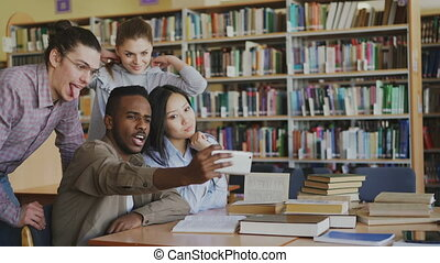 Group of international students have fun smiling and making selfie photos on smartphone camera at university library. Cheerful friends have rest while prepare for examination