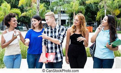 Group of international students walking on campus of university