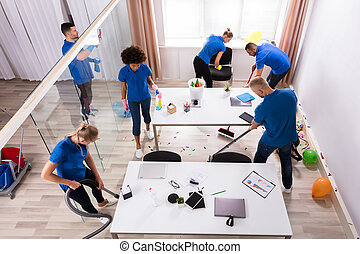 Group Of Janitors Cleaning Office With Cleaning Equipment