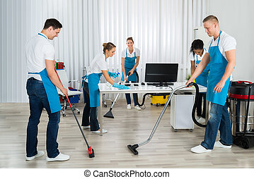 Group Of Janitors Cleaning The Office