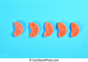 group of jelly candies piece of orange fruit bottles on blue background