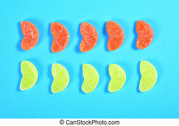 group of jelly candies piece of orange fruit color yellow and orange on blue background