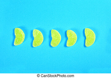 group of jelly candies piece of orange fruit on blue background