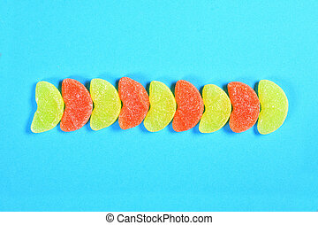 group of jelly candies piece of orange fruit orange and yellow color on blue background