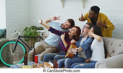Group of joyful friends taking selfie photos on smartphone camera while celebrating at party with beer and snacks at home