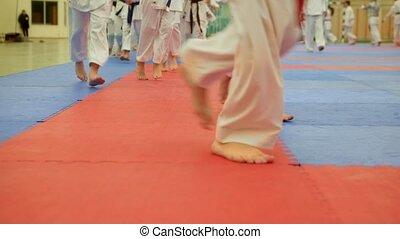 Group of karateka teenagers in kimono runs on tatami in the...