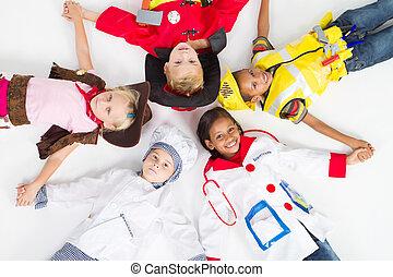group of kids in various uniforms lying on floor