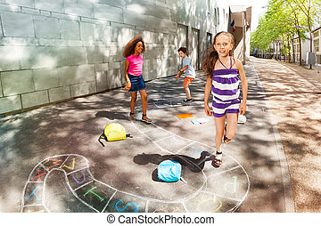 Group of kids play hopscotch near school jumping one after ...