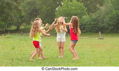 Group of kids play with soap bubbles in a park. Children active game. Slow motion
