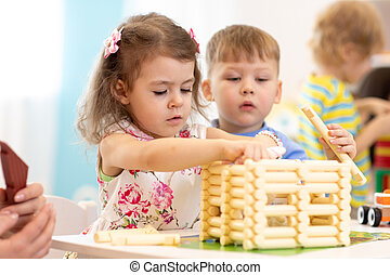 Group of kids playing in kindergarten. Children building toy house with blocks sitting together by the table