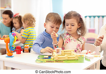 Group of kids playing in kindergarten. Children building toy house with plastic blocks sitting together by the table
