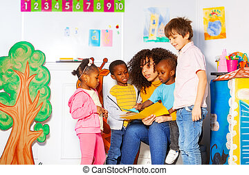 Group of kids reading book with teacher in nursery