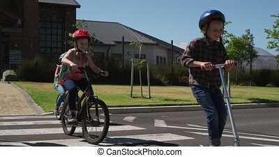 Group of kids riding bicycles and scooter and crossing the ...
