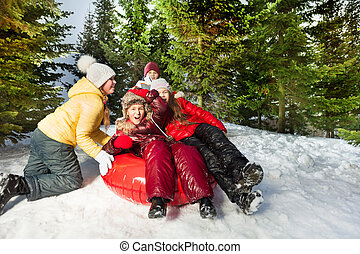 Group of kids riding down hill on red ice-boat