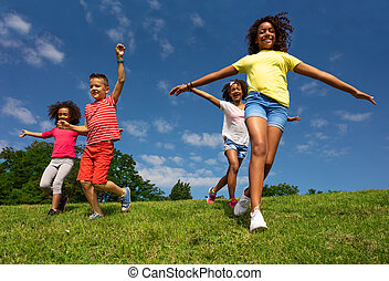 Group of kids run downhill with happy expression