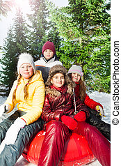 Group of kids sitting on the sledge in park