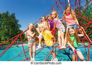 Group of kids sitting together on red ropes