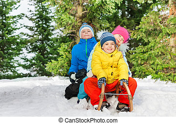 Group of kids slide down on sledge in the park