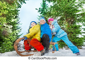 Group of kids slide down the hill on sledge