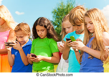 Group of kids sms - Group of busy kids looking at their...